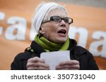 """Small photo of LONDON, UK - DECEMBER 12, 2015 Unidentified campaigner reads a poem on the environment at the Campaign Against Climate Change """"Red Line"""" protest opposite Houses of Parliament."""