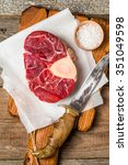 Small photo of Raw fresh cross cut veal shank and meat cleaver for making Osso Buco on wooden background, top view