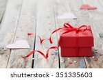 Stock photo gift box with red bow ribbon and paper heart on wooden table for valentines day 351335603