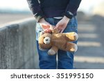 Stock photo dramatic portrait of a little homeless boy holding a teddy bear poverty city street 351995150