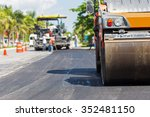 Small photo of Road construction works with steamroller machine and asphalt finisher