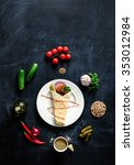Small photo of Falafel on a white plate with ingredients laid out on a spiral on a blackboard. View from above