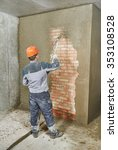 Small photo of Plasterer operating sprayer equipment machine for spraying thin-layer putty plaster finishing on brick wall