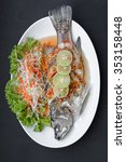 Small photo of Steamed snapper with lemon on black background. Top view
