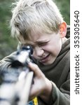 Small photo of Portrait of little boy with airgun shooting outdoors, air rifle with telescopic sights