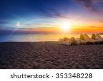 calm sea waves touch  sandy beach with few boats at sunset and full moon - stock photo