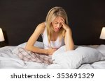 woman in pain sitting in bed  | Shutterstock . vector #353691329