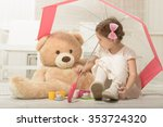 Expressive beautiful little girl having a tea party with her teddy bear, sitting under umbrella, indoor. - stock photo