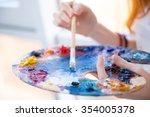 closeup of paintbrush in woman... | Shutterstock . vector #354005378
