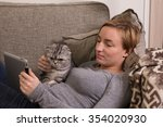 Stock photo an adult caucasian girl is lying on a sofa holding tablet pc and hugging a cat both of them are 354020930