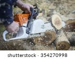 A Person Using A Chainsaw On...