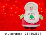 Small photo of Toy Santa Claus My first Santa on red bokeh background. Xmas time background. Merry christmas card. Winter holidays. Xmas theme. Happy New Year.