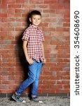 cute little boy on brick wall... | Shutterstock . vector #354608690