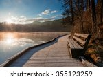 bench by the lake at sunrise.... | Shutterstock . vector #355123259