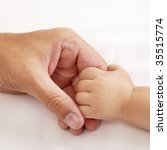 Baby holding dads hand - stock photo