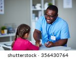 Small photo of African-American clinician talking to little patient at hospital