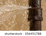 Rusty burst pipe spraying water ...