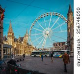 Small photo of View over plaza in Ghent, Belgium, with a traditional Christmas wheel and a film emulation cyan sky and warmer tones and colors. Available in high resolution panorama square format for large prints
