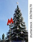 "Small photo of MOSCOW, RUSSIA - DEC 29, 2015:Letter ""M"" - symbol of Moscow Metro on background of Christmas tree near monument to great Russian poet Alexander Pushkin"