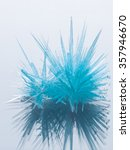 Small photo of beautiful bright unusual blue crystal ammonium phosphate on a gray background with reflection