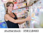lady arranging magazines on... | Shutterstock . vector #358118483