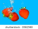 Strawberries bursting into refreshing cool blue water. - stock photo