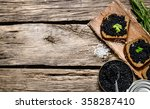 Small photo of Sandwiches with black caviar, a jar of caviar and a spoon. On a wooden table. Free space for text . Top view