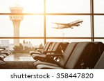 Small photo of Empty chairs in the departure hall at airport , with the control tower and an airplane taking off at sunset. Travel and transportation concepts.