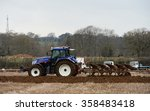 Small photo of WINGFIELD, UK - APR 4, 2015: A tractor pulls a plough through a field. Widespread use of tractors emerged during the mechanisation of the agricultural industry in the 1950s.
