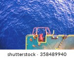 Small photo of Offshore workers working together preparing the barge anchor fairlead for anchor deployment