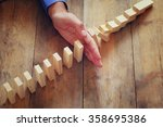 a male hand stoping the domino... | Shutterstock . vector #358695386