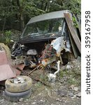 Small photo of A discarded van in woodland that has been pillaged for parts and scrap