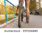 Surface Level View of YOung Man Riding Bicycle with Close Up on Rear Tire - Rider Taking a Break While Riding on Waterfront Path with Colorful Railing in Urban Park on Autumn Day