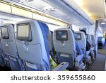 Passengers sitting in tourist class seats inside an airplane - stock photo