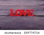 Small photo of Love text on wooden background