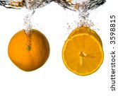 A whole orange and slices dropped onto water. - stock photo