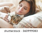 Stock photo girl lying in bed with her cat 360999083