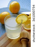 Small photo of Glass of fresh lemonade with a reamer in portrait