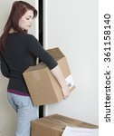 Small photo of Dejected and sad young red-haired woman carrying moving boxes out interior door as eviction notice is visible in lower right of frame.