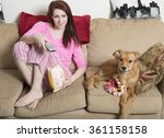 Small photo of Cute young red-haired woman in pink pajamas sitting in living room eating popcorn with her adorable dog next to her on couch - watching tv