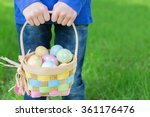 little boy with no face visible holding basket full of colorful easter eggs standing on the grass in the park after egg hunt