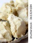 Small photo of Unrefined raw shea butter on wooden background