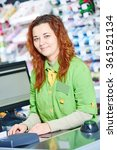 Small photo of supermarket cashier worker at check out cashdesk in shop store