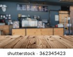 Stock photo wood table top on blur coffee shop background 362345423