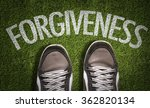 Small photo of Top View of Sneakers on the grass with the text: Forgiveness
