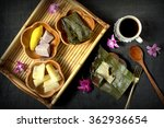 Small photo of A set of food, boil cassava or tapioca, Sweeyt potato, yam, coffee and cake wrapped in banana leaf. on bambooo tray. antique coth