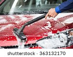 Cropped image of mature washer cleaning red car at service station - stock photo
