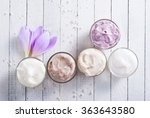Small photo of beauty product samples and autumn crocus herbal flower on white wooden table