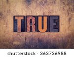 "Small photo of The word ""True"" written in dirty vintage letterpress type on a aged wooden background."