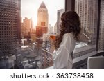 Stock photo beautiful woman holding coffee cup and looking to the window in luxury manhattan penthouse 363738458